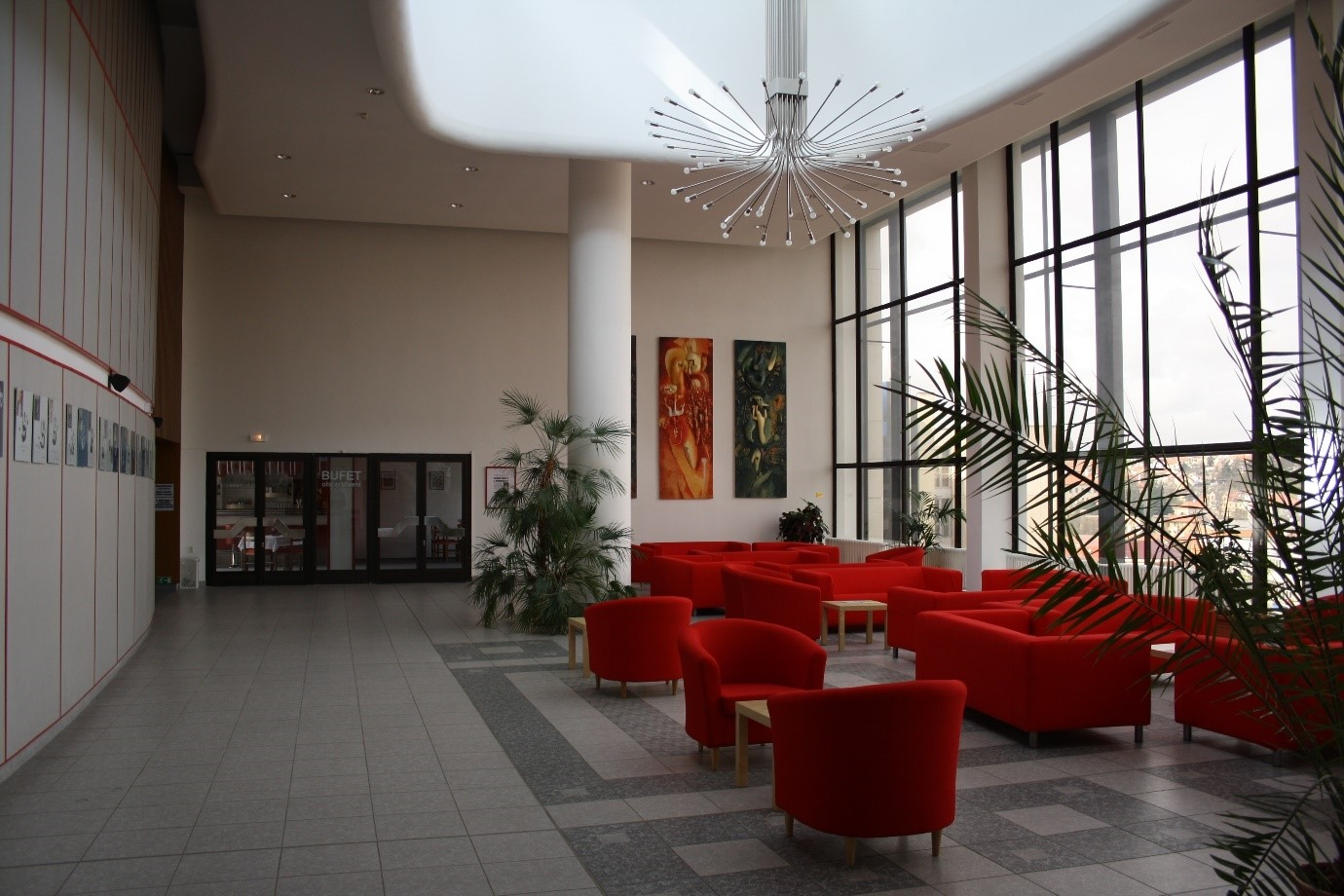 modern hotel foyer with red tub chairs and large windows